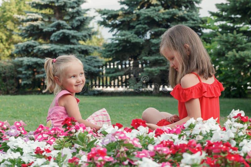 Δύο ξανθά κορίτσια με κόκκινα και ροζ φορέματα στοκ εικόνα