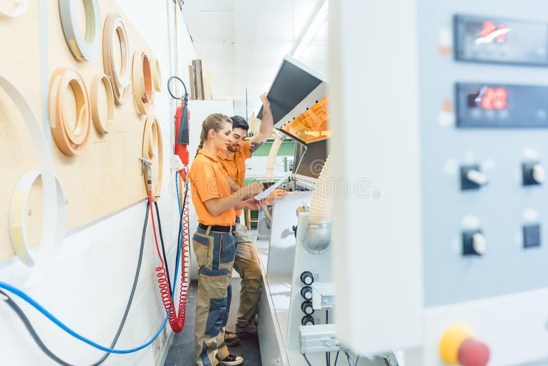 Δύο ξυλουργοί που καθαρίζουν τη μηχανή καπλαμάδων στο εργαστήριο στοκ φωτογραφία
