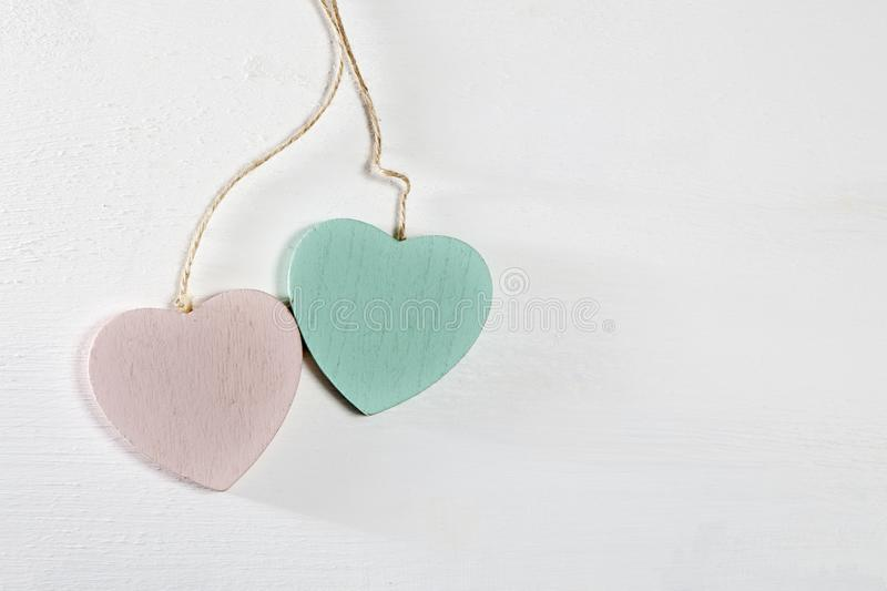 Δύο ξύλινες καρδιές κρεμούν σε έναν άσπρο ξύλινο τοίχο στοκ εικόνες