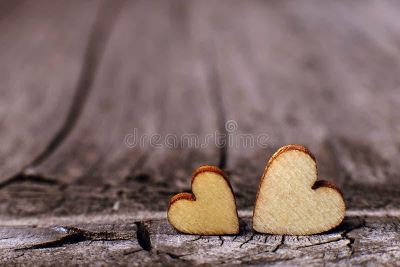Δύο ξύλινες καρδιές που τοποθετούνται ωραία σε ένα εκλεκτής ποιότητας ξύλινο υπόβαθρο Διάστημα αντιγράφων, έννοια αγάπης στοκ φωτογραφίες