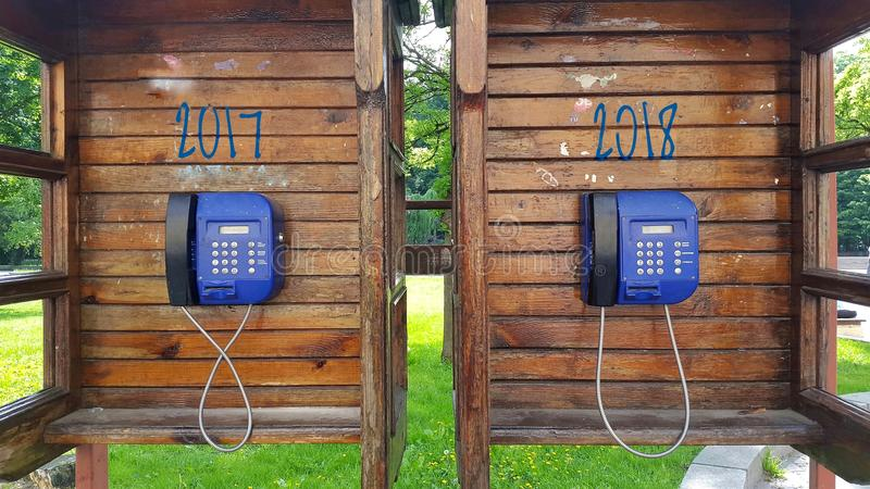 Δύο ξύλινοι τηλεφωνικοί θάλαμοι με τα τηλέφωνα αμοιβής Η έννοια για το νέο έτος έως 2018 στοκ φωτογραφία με δικαίωμα ελεύθερης χρήσης