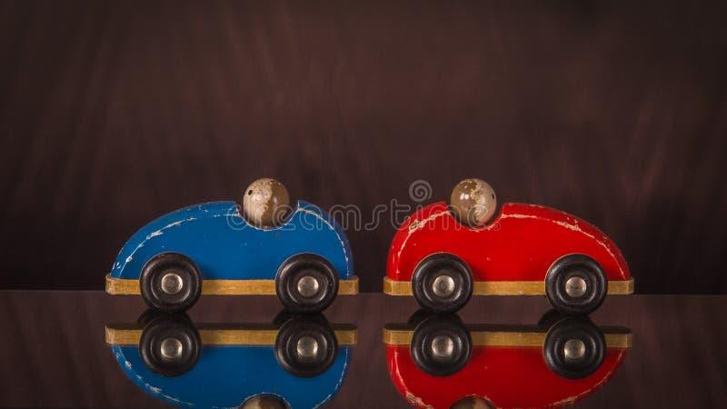 Δύο ξύλινα αυτοκίνητα παιχνιδιών κόκκινος και μπλε με τα άτομα στοκ φωτογραφίες