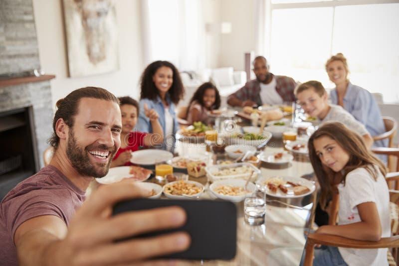 Δύο οικογένειες που παίρνουν Selfie δεδομένου ότι απολαμβάνουν το γεύμα στο σπίτι από κοινού στοκ εικόνες