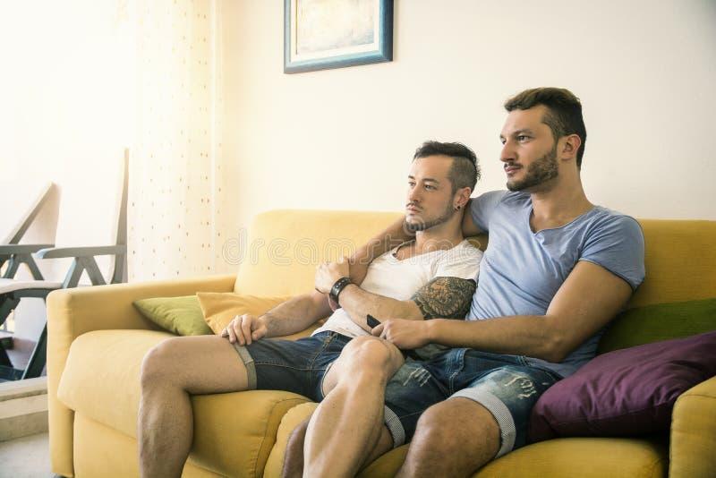 Δύο ομοφυλόφιλοι στον καναπέ που αγκαλιάζει στο σπίτι στοκ φωτογραφία