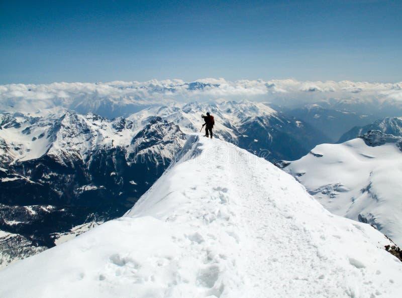 Δύο ορειβάτες βουνών σε μια στενή και εκτεθειμένη κορυφογραμμή κορυφών που κοιτάζει πέρα από την άκρη στοκ εικόνα