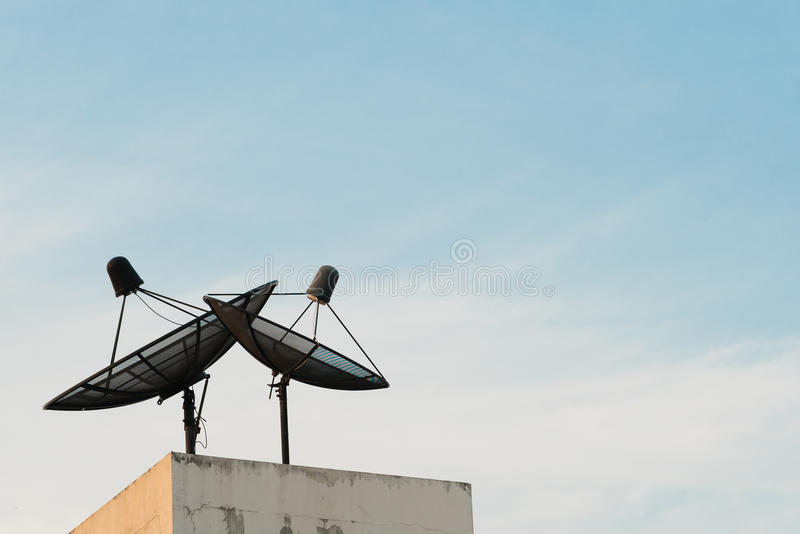Δύο δορυφορικά πιάτα κατά τη διάρκεια του ηλιοβασιλέματος με το διάστημα αντιγράφων στο υπόβαθρο μπλε ουρανού στοκ φωτογραφία με δικαίωμα ελεύθερης χρήσης