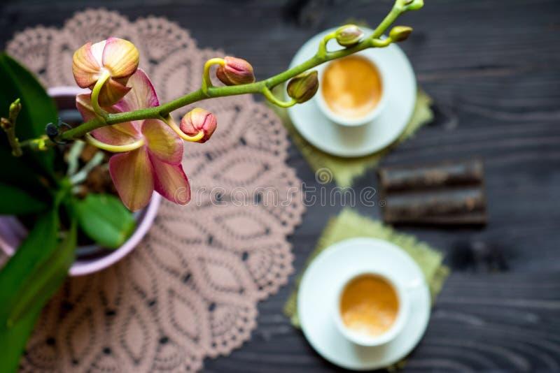 Δύο λουλούδι φλιτζανιών του καφέ και ορχιδεών στοκ φωτογραφία