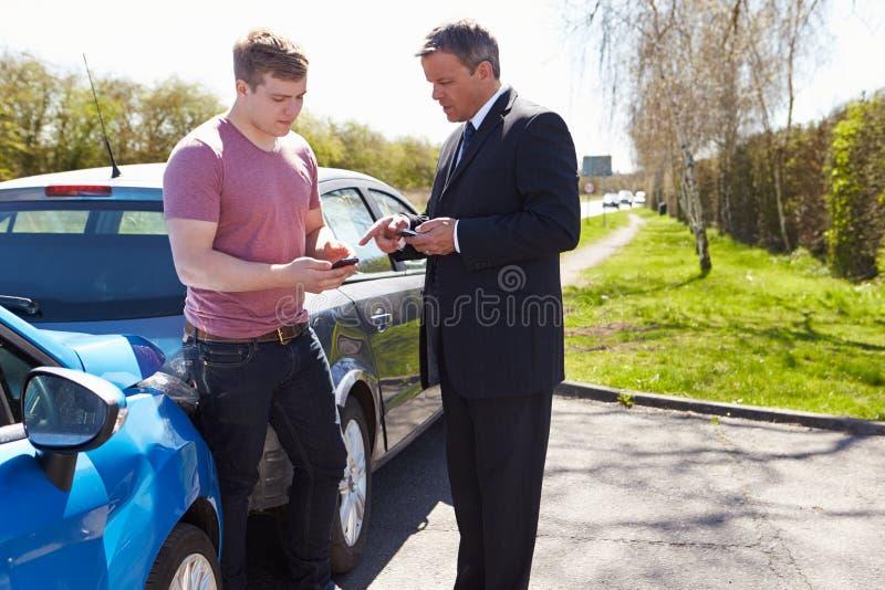 Δύο οδηγοί ανταλλάσσουν τις ασφαλιστικές λεπτομέρειες μετά από το ατύχημα στοκ φωτογραφία με δικαίωμα ελεύθερης χρήσης