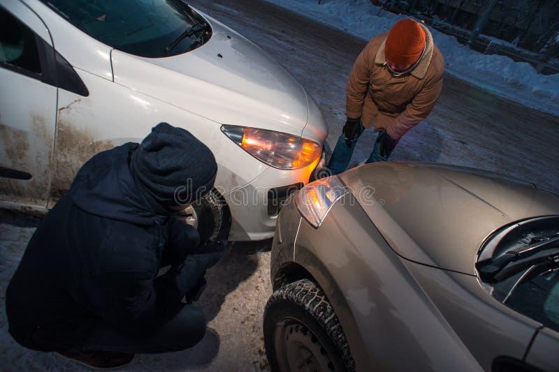 Δύο οδηγοί μετά από τη σύγκρουση αυτοκινήτων στη χειμερινή οδό στοκ φωτογραφίες