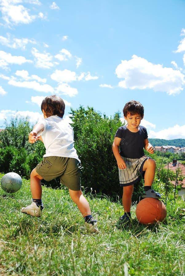 Δύο παιδάκια με την καλαθοσφαίριση και το ποδόσφαιρο στοκ φωτογραφία με δικαίωμα ελεύθερης χρήσης