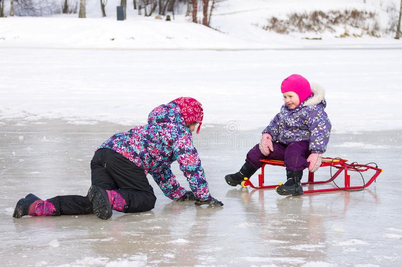 Δύο παιδιά έχουν τη συνεδρίαση διασκέδασης μαζί στον πάγο και παιχνίδι με ένα έλκηθρο χιονιού μια σαφή χειμερινή ημέρα στοκ φωτογραφία με δικαίωμα ελεύθερης χρήσης