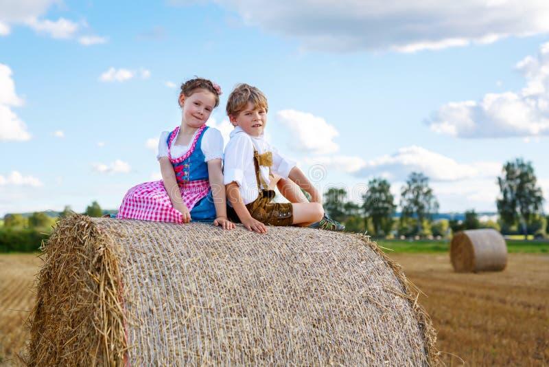 Δύο παιδιά, αγόρι και κορίτσι στα παραδοσιακά βαυαρικά κοστούμια στον τομέα σίτου στοκ φωτογραφία με δικαίωμα ελεύθερης χρήσης