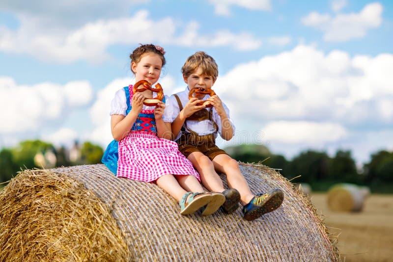 Δύο παιδιά, αγόρι και κορίτσι στα παραδοσιακά βαυαρικά κοστούμια στον τομέα σίτου στοκ εικόνες με δικαίωμα ελεύθερης χρήσης