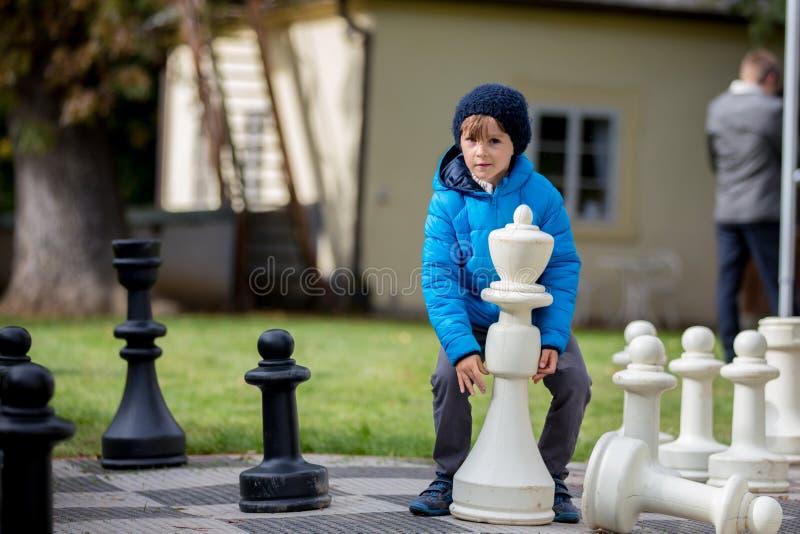Δύο παιδιά, αδελφοί αγοριών, σκάκι παιχνιδιού με τους τεράστιους αριθμούς στο τ στοκ εικόνα