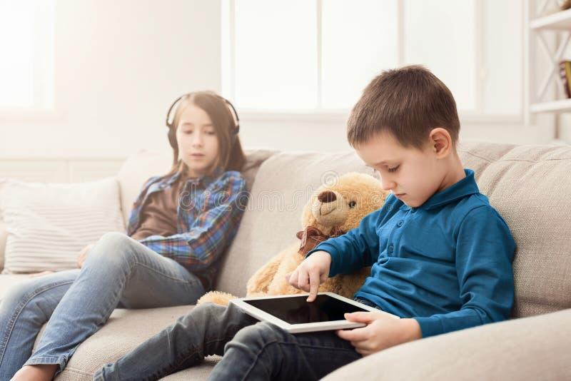 Δύο παιδιά με τις συσκευές στον καναπέ στο σπίτι στοκ φωτογραφίες με δικαίωμα ελεύθερης χρήσης
