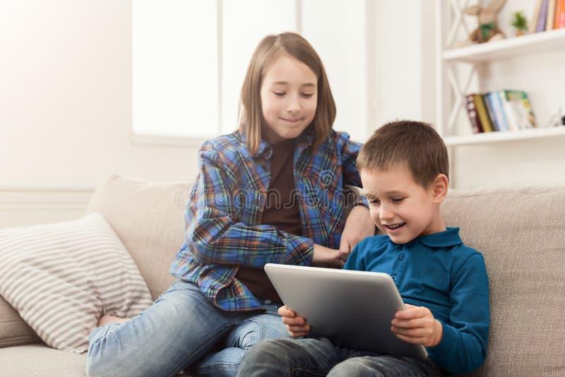 Δύο παιδιά με τις συσκευές στον καναπέ στο σπίτι στοκ φωτογραφία