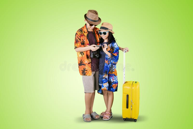 Δύο παιδιά με το τηλέφωνο και τις αποσκευές στο στούντιο στοκ εικόνα