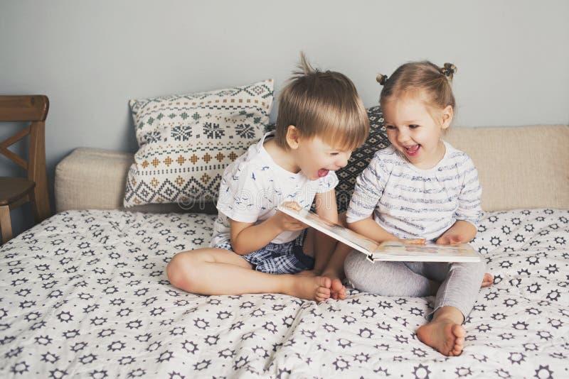 Δύο παιδιά που κάθονται στο κρεβάτι και που διαβάζουν ένα βιβλίο στοκ εικόνες με δικαίωμα ελεύθερης χρήσης
