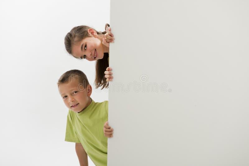 Δύο παιδιά που κρατούν ένα κενό σημάδι στοκ φωτογραφία με δικαίωμα ελεύθερης χρήσης