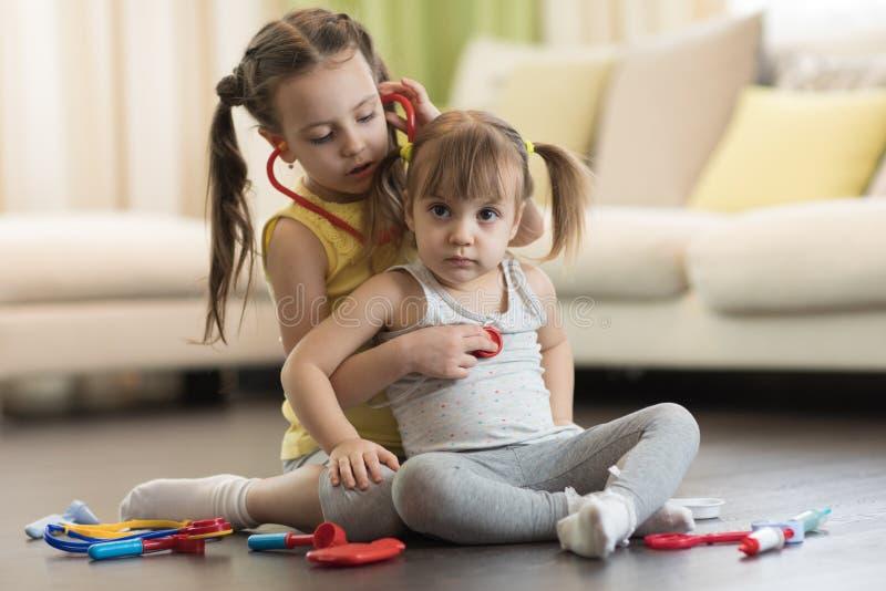 Δύο παιδιά preschooler, χαριτωμένο κορίτσι μικρών παιδιών και η παλαιότερη αδελφή παιδιών, ο παίζοντας γιατρός και το νοσοκομείο  στοκ φωτογραφίες