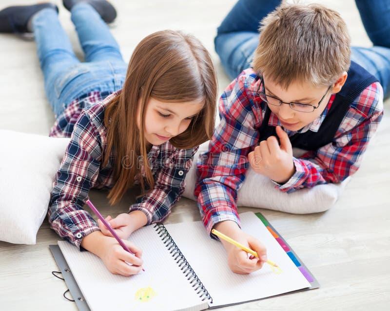 Δύο παιδάκια που σύρουν με τα κραγιόνια στοκ εικόνα με δικαίωμα ελεύθερης χρήσης