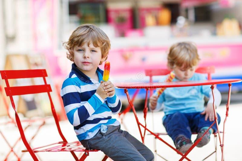 Δύο παιδιά - αγόρια αμφιθαλών που τρώνε το ζωηρόχρωμο παγωτό το καλοκαίρι στοκ εικόνα με δικαίωμα ελεύθερης χρήσης