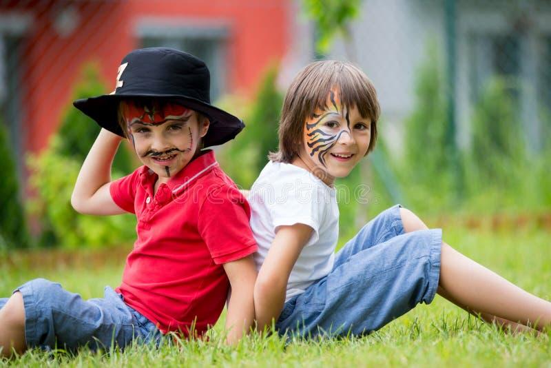Δύο παιδιά, αδελφοί, χρωμάτισαν ως τίγρη και πειρατής, που παίζουν μέσα στοκ εικόνα με δικαίωμα ελεύθερης χρήσης