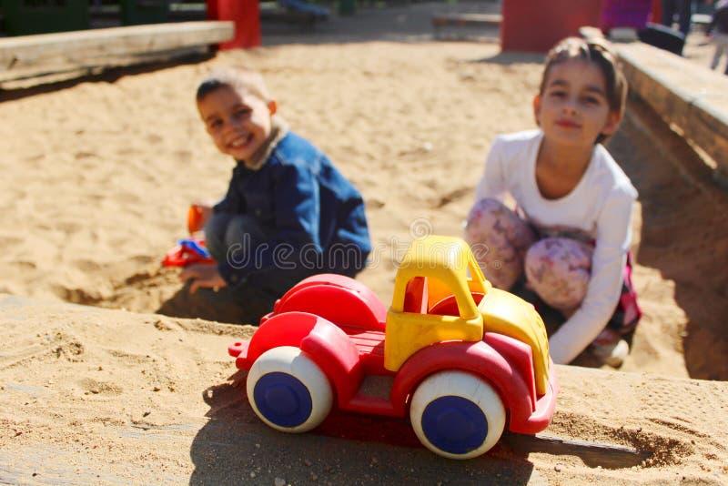 Δύο παιδιά που παίζουν μαζί στο σκάμμα στοκ φωτογραφία με δικαίωμα ελεύθερης χρήσης