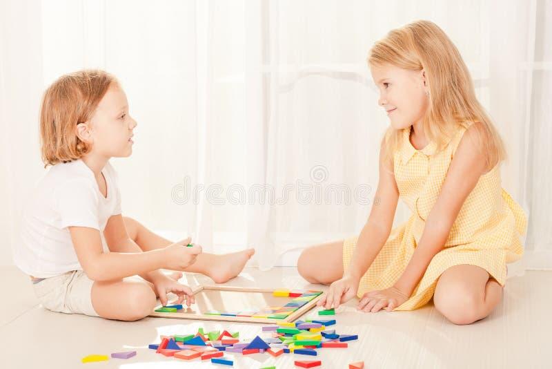 Δύο παιδιά που παίζουν με το ξύλινο μωσαϊκό στο δωμάτιό τους στοκ φωτογραφία