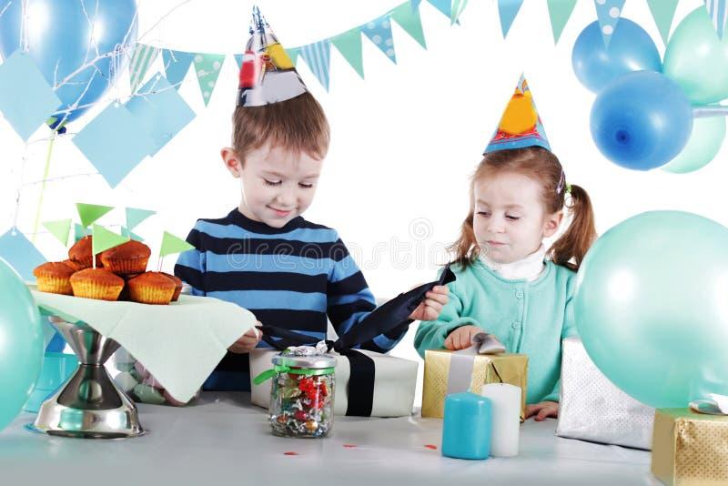 Δύο παιδιά στο μπλε κόμμα παρουσιάζουν το ανοίγοντας παρόν στοκ φωτογραφίες