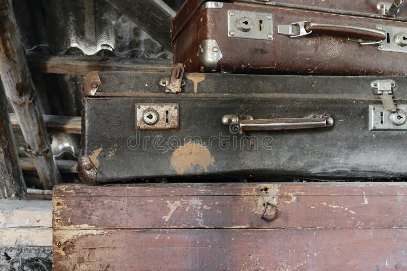 Δύο παλαιές, σκουριασμένες, σκονισμένες και βρώμικες βαλίτσες που βρίσκονται στο καφετί στήθος στοκ εικόνα