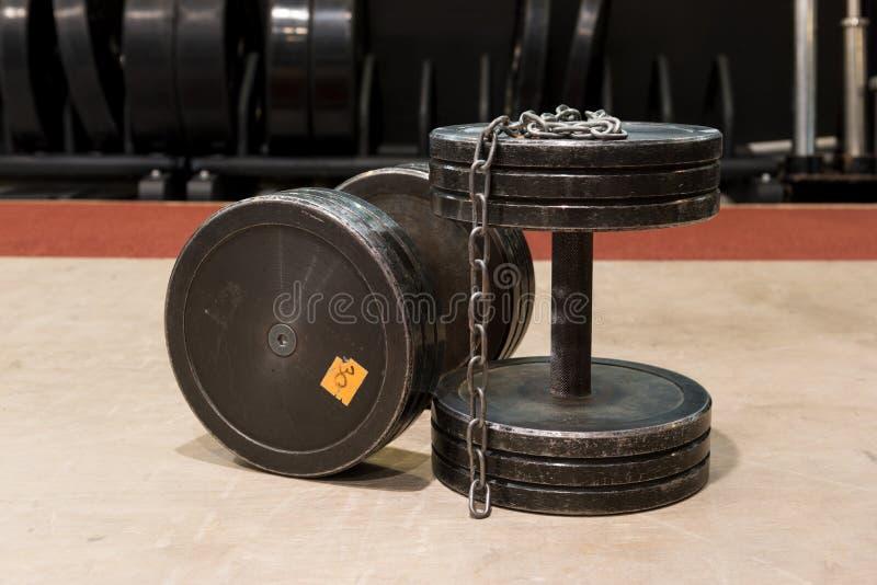 Δύο παλαιοί και χρησιμοποιημένοι αλτήρες μετάλλων γυμναστικής μαύροι με την ασημένια αλυσίδα Εξοπλισμός γυμναστικής στοκ εικόνες