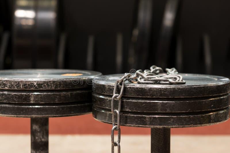 Δύο παλαιοί και χρησιμοποιημένοι αλτήρες μετάλλων γυμναστικής μαύροι με την ασημένια αλυσίδα Εξοπλισμός γυμναστικής στοκ φωτογραφίες