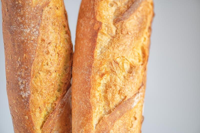 Δύο παραδοσιακά γαλλικά baguettes, που απομονώνονται στο γκρίζο υπόβαθρο στοκ εικόνα