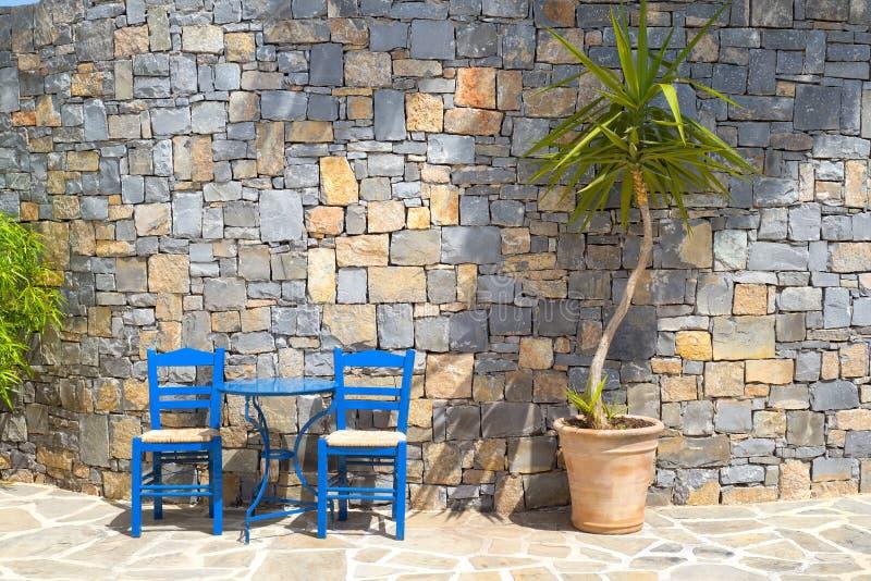 Δύο παραδοσιακές ξύλινες καρέκλες και ένας πίνακας μετάλλων κοντά σε έναν τοίχο πετρών στοκ εικόνες με δικαίωμα ελεύθερης χρήσης