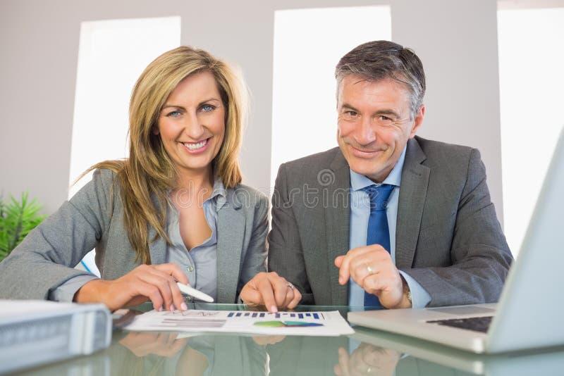 Δύο παρακαλεσμένοι επιχειρηματίες που χαμογελούν στη κάμερα που αναλύει ένα graphi στοκ φωτογραφία με δικαίωμα ελεύθερης χρήσης