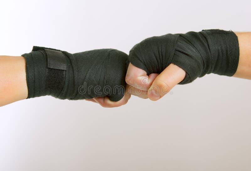 Δύο παραδίδουν έναν μαύρο εγκιβωτίζοντας βραχίονα επιδέσμων παλεύοντας, στοκ εικόνες με δικαίωμα ελεύθερης χρήσης