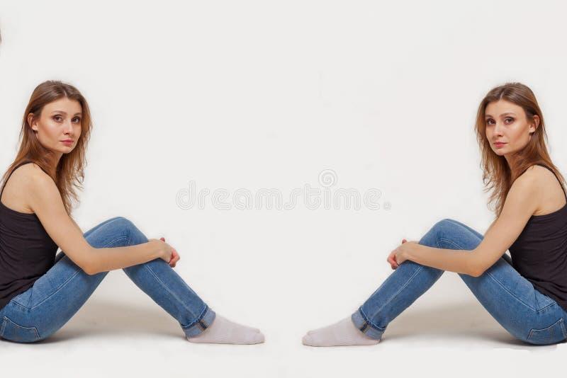 Δύο παρόμοιες νέες γυναίκες κάθονται πίσω στις πλευρές της εικόνας στοκ φωτογραφία