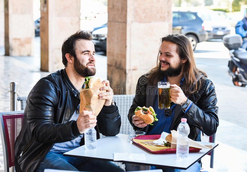 Δύο πεινασμένοι φίλοι/τουρίστες τρώνε το μεσημεριανό γεύμα μαζί και χαμογελούν στοκ εικόνα με δικαίωμα ελεύθερης χρήσης