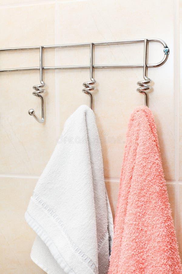 Δύο πετσέτες υφασμάτων που κρεμούν τα αγκίστρια στοκ εικόνες