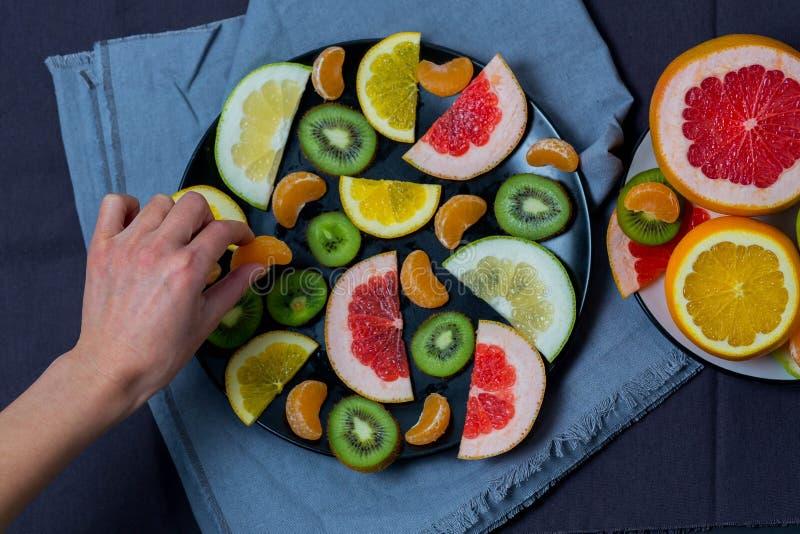 Δύο πιάτα με τα κομμένα φρούτα, φωτεινό juicy εσπεριδοειδές σε ένα μπλε γκρίζο σκοτεινό υπόβαθρο κουρελιών πετσετών κουζινών, το  στοκ εικόνες