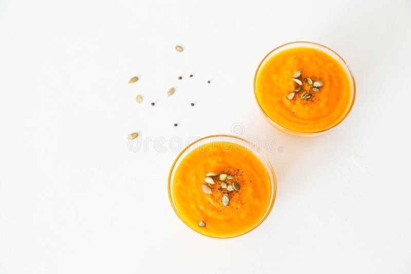 Δύο πιάτα της σούπας κολοκύθας με τους σπόρους σε ένα άσπρο υπόβαθρο με το διάστημα για το κείμενό σας στοκ φωτογραφίες