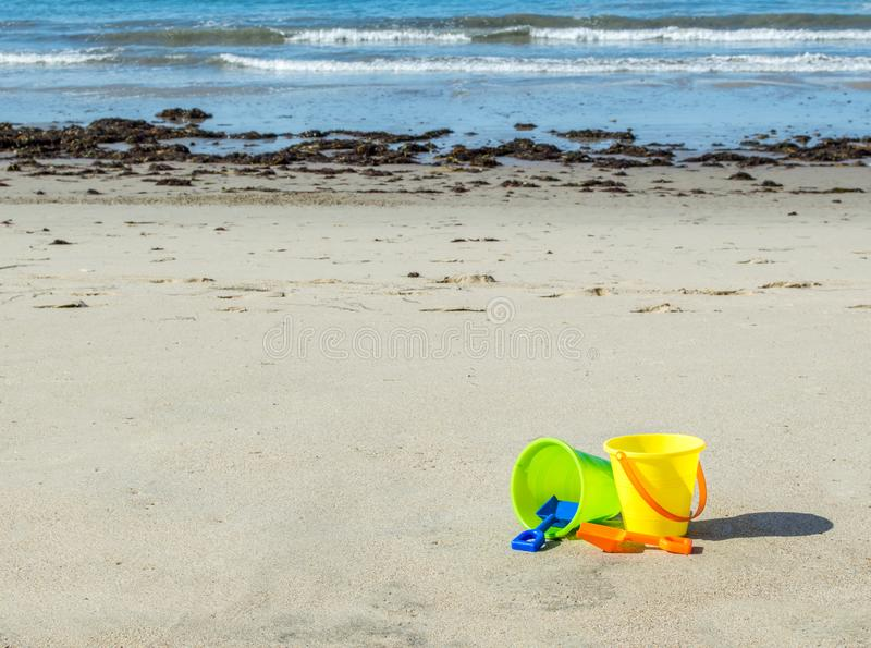 Δύο πλαστικοί κάδοι άμμου με τα φτυάρια σε μια αμμώδη παραλία στοκ φωτογραφίες με δικαίωμα ελεύθερης χρήσης