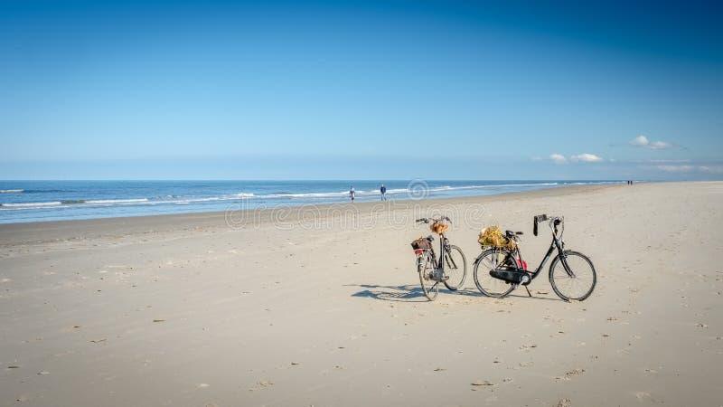 Δύο ποδήλατα στην παραλία Schiermonnikoog που περιμένει τους ιδιοκτήτες τους στοκ εικόνες