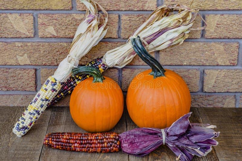 Δύο πορτοκαλιές κολοκύθες με το πολύχρωμο ινδικό καλαμπόκι στο αγροτικό ξύλο στοκ εικόνα με δικαίωμα ελεύθερης χρήσης