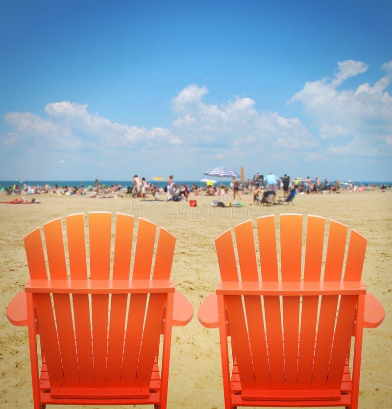 Δύο πορτοκαλιές έδρες παραλιών στην άμμο στοκ φωτογραφία