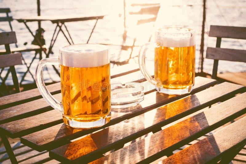 Δύο ποτήρια της ελαφριάς μπύρας με τον αφρό σε έναν ξύλινο πίνακα Σε μια βάρκα Κόμμα κήπων Φυσική ανασκόπηση αλκοολών Μπύρα σχεδί στοκ φωτογραφία