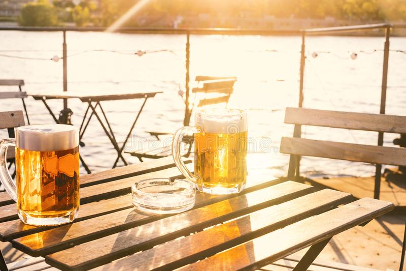 Δύο ποτήρια της ελαφριάς μπύρας με τον αφρό σε έναν ξύλινο πίνακα Σε μια βάρκα Κόμμα κήπων Φυσική ανασκόπηση αλκοολών Μπύρα σχεδί στοκ εικόνες με δικαίωμα ελεύθερης χρήσης