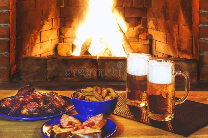 Δύο ποτήρια της μπύρας με τα πρόχειρα φαγητά σε έναν ξύλινο πίνακα κοντά στην εστία στοκ εικόνα με δικαίωμα ελεύθερης χρήσης
