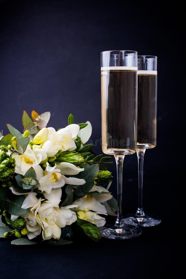 Δύο ποτήρια της σαμπάνιας και ανθοδέσμη των άσπρων λουλουδιών στοκ εικόνες